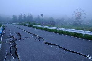 手前の道路は震災で破損